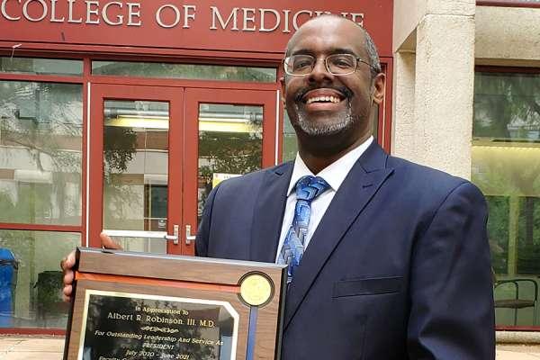 Doctor Robinson holding his leadership award