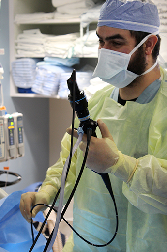 Fellow performing a trach procedure