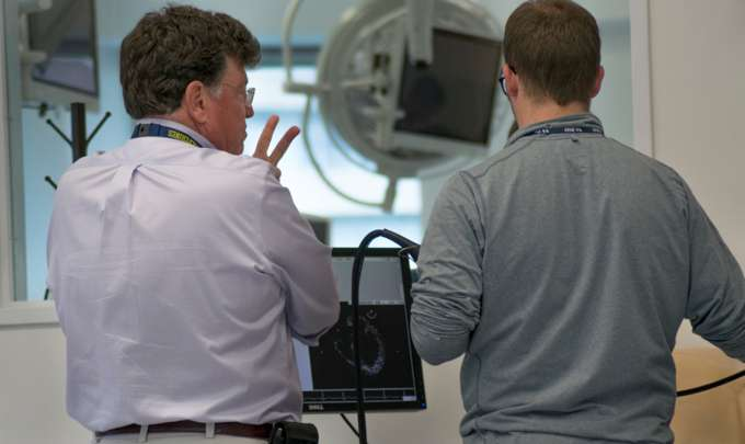 Dr. McGough working on a simulator with a fellow