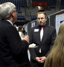 Doctor Cam Smith discussing research at the event
