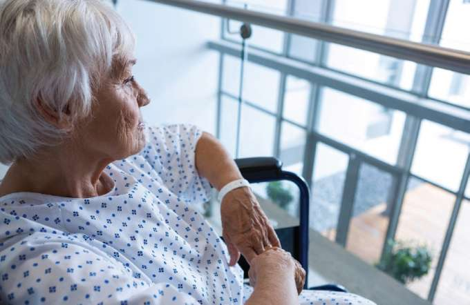 Senior woman in hospital gown looking out the window