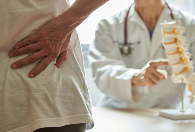 Patient with back pain and a doctor showing her a skeleton of a spine