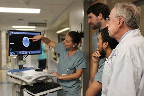 Fellows and attending looking at a scan