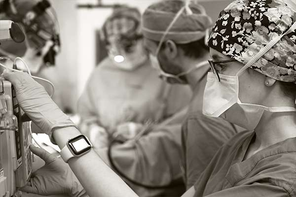 Close up of an anesthesiologist in the O-R with others working in the background